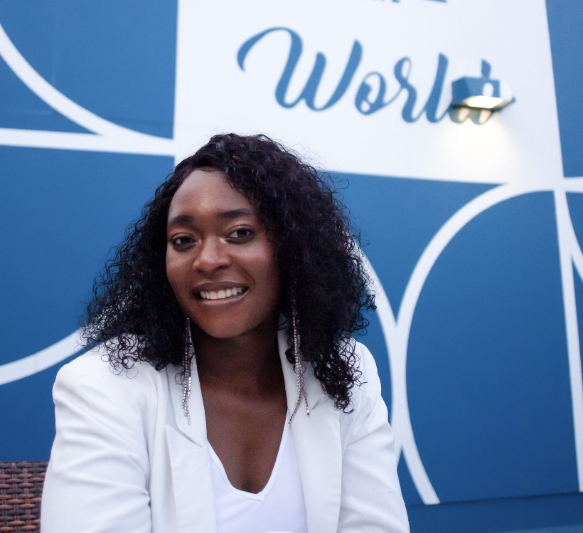 The image shows Fatmatta sitting down with curly hair wearing a white jacket and white shirt in front of a blue wall with circle designs and a quote.