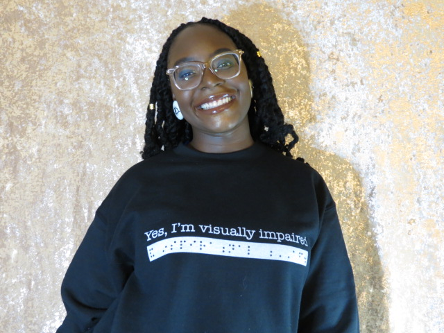 "The image shows Fatmatta smiling while standing behind a yellow background and wearing a black turtleneck. Text and braille says ""Yes, I'm visually impaired"""