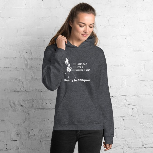 "Dark heather gray hoodie w/white ink. Fashion icon Abby is to the left of a checklist ""Handbag, Heels, White Cane."" Directly under her and the checklist is the slogan: ""Ready to Conquer"""