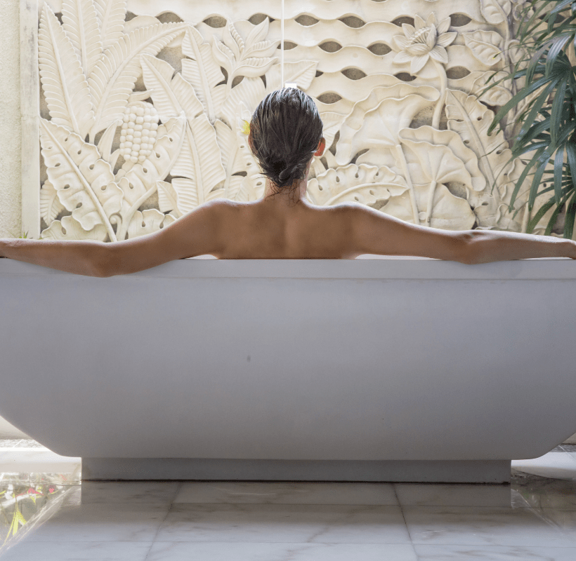 Photo of a young woman relaxing in the bathtub at a luxury hotel spa.