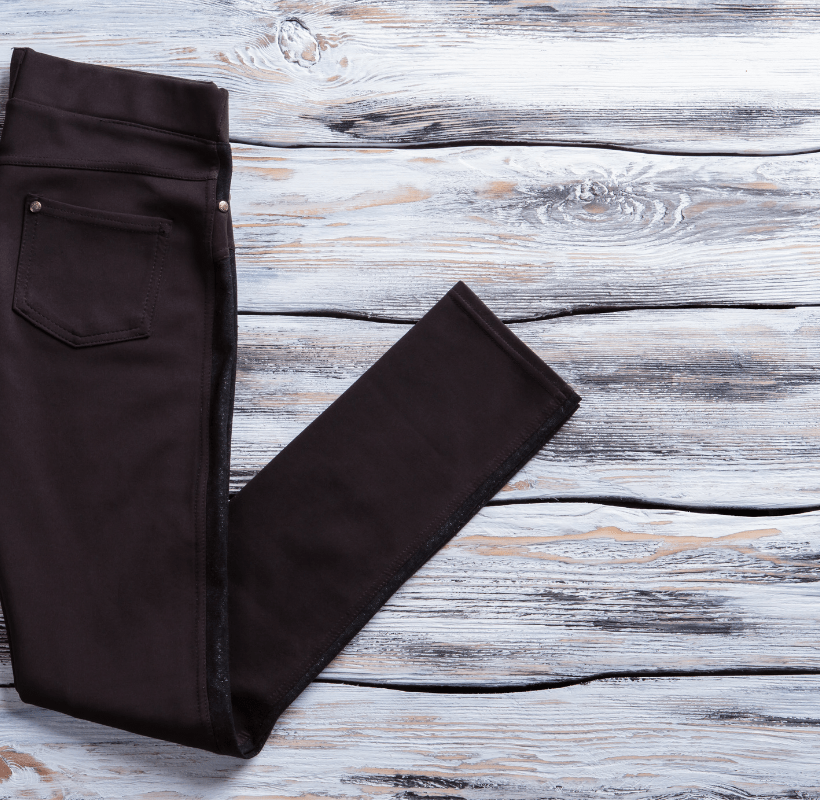 Lady's casual black pants on a wooden background.