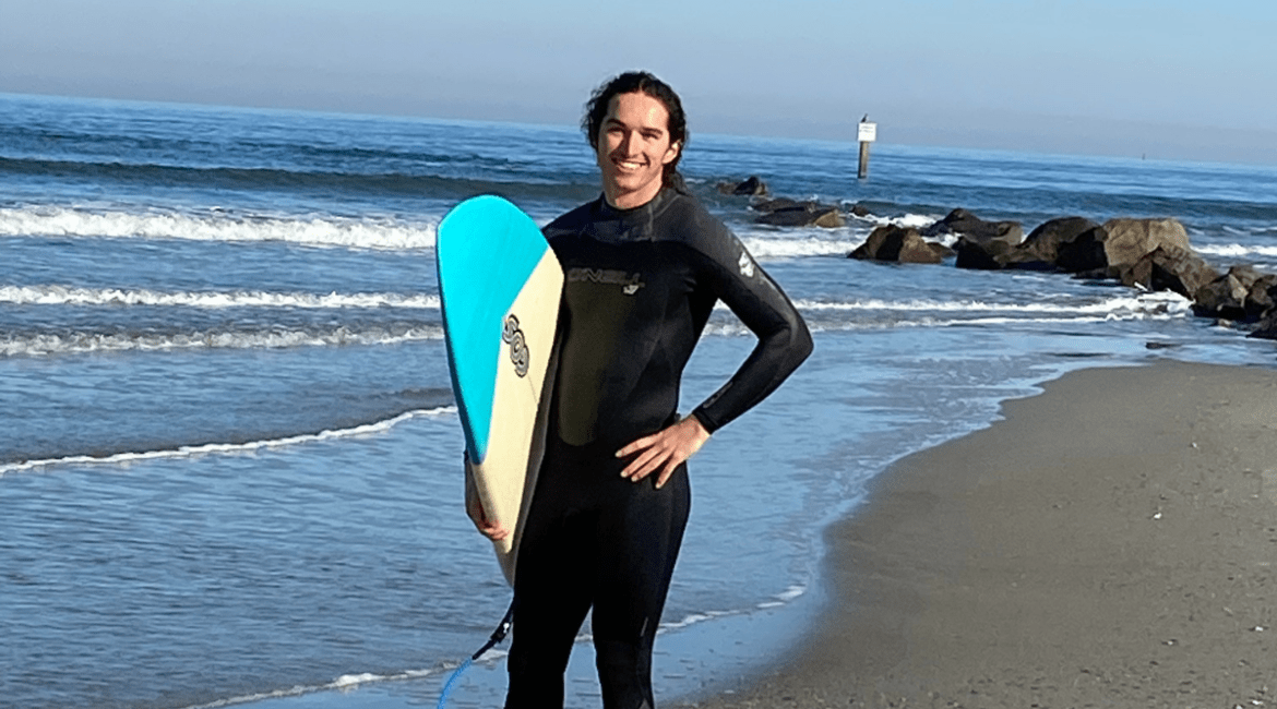 The featured image is a surf photo of Kai smiling while standing on the beach in a black wet suit holding his skimboard. His long dark wavy hair is pulled back in a ponytail.