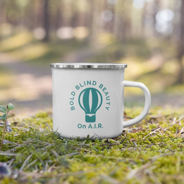 """White enamel mug with a silver rim. The podcast logo is a teal-colored illustration of a hot air balloon with the words """"Bold Blind Beauty"""" curved around the top of the balloon. Under the balloon are the words """"On A.I.R."""" The logo is to the right and left of the handle."""