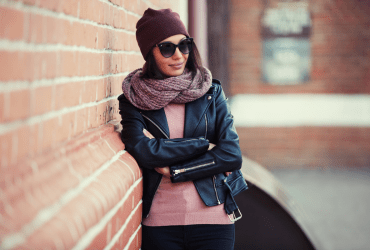 Young fashionable woman in black leather jacket, pink sweater, sunglasses, burgundy knit cap, chunky cozy mauve scarf wrapped around her neck.