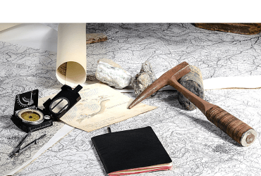 Photo contains items for a geological expedition among them a map, compass, pick, writing pad, rocks.