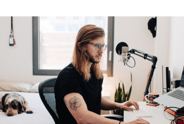 The header is a photo of Lance with long blonde hair, beard, and mustache at work podcasting. In the shot, he is wearing eyeglasses while sitting at his desk with a professional microphone, plant, and coffee cup nearby. Lance has on a black tee which exposes a cool tattoo on his right bicep.