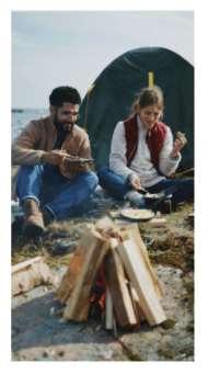 A couple enjoys breakfast while camping outdoors by the sea. They are dressed in fleece sweaters, denim jeans, and boots and are seated close to a small campfire. The scene is cozy and peaceful as they smile, eat and exchange light conversation.