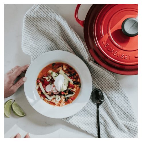 A closeup of Le Creuset's Signature 5.5 Quart Dutch Oven in Cerise Red beside a colorful bowl of homemade chicken vegetable soup with garnishes of avocado, sour cream, and lime wedges.