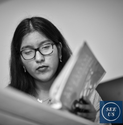 "The fifth photo is identical to the header (a black and white photo from the ""See Us"" book. Karla was reading a book relating to the U.S History portion of the USCIS Citizenship exam.)"