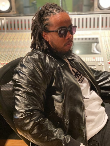 In this photo, Jahron is sitting wearing a black leather jacket with a white shirt and his signature sunglasses.