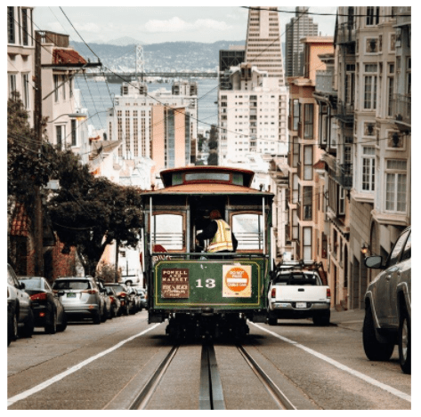A sunny, long shot view of a San Francisco cable car as it moves down the tracks of a steep street. The green and red cable car with cables overhead is labeled with the number 13 and has 3 destinations: Powell and Market, Hyde and Beach and Fisherman's Wharf. The street is lined with multi-story homes with bay windows. The San Francisco Bay and Bay Bridge are in the distance