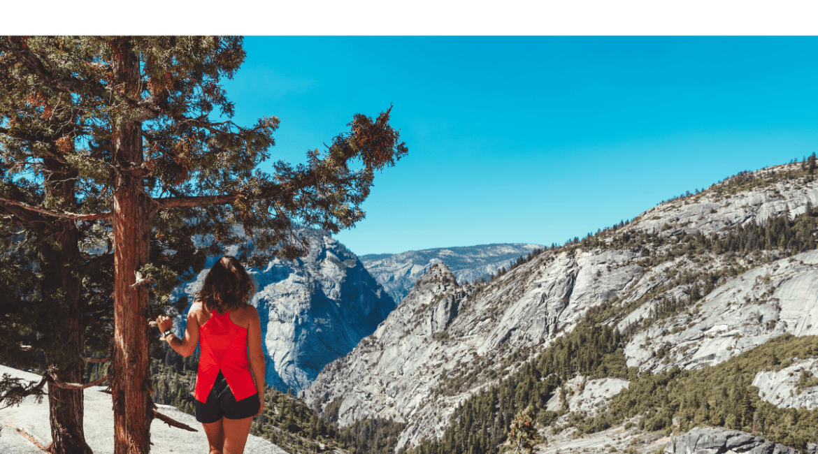 Young woman hiking scenic trails in Yosemite National Park. She is standing next to a couple of evergreen trees and in the background are mountains mountains dotted with green patches of greenery against a blue sky.