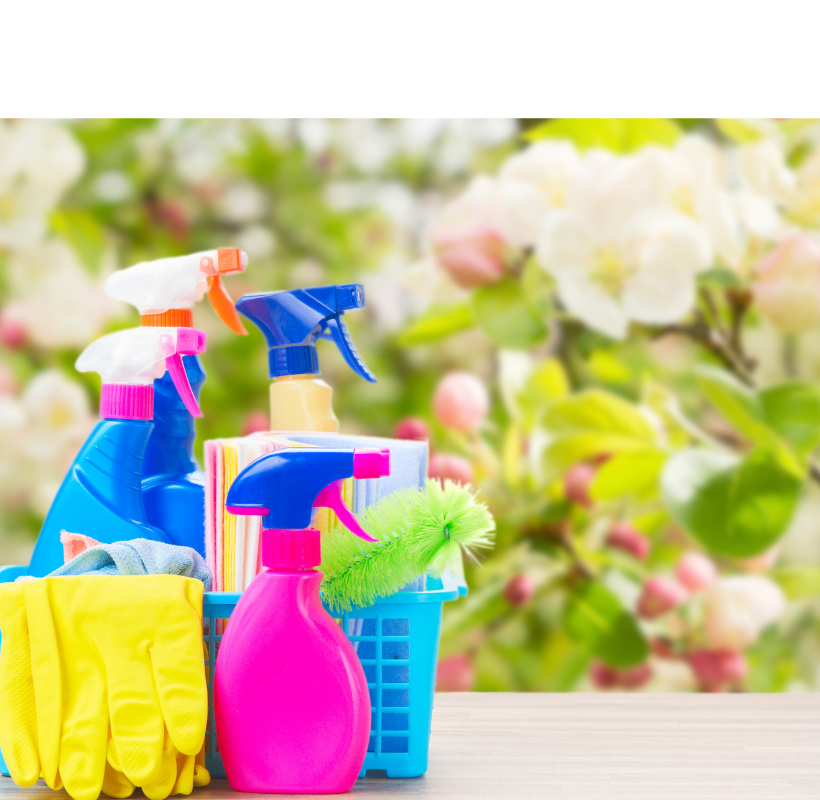 Assortment of different colored plastic cleaning bottles in a basket with yellow rubber gloves. In the background is a blurred floral spring backdrop.