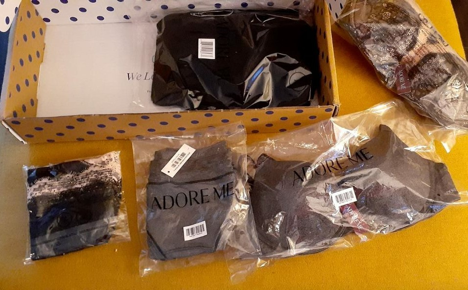 Adore Me Elite Box with gray bra/panty set, black lace bra/panty set, and a black dress.