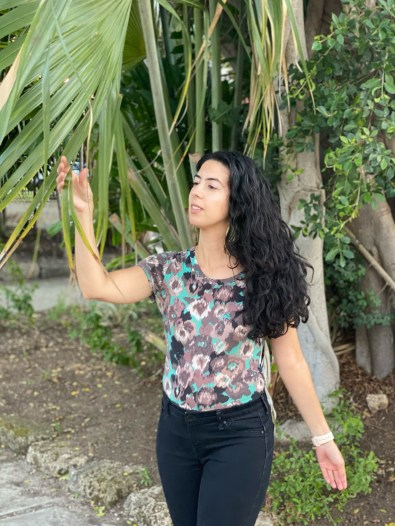 Catarina is standing near some green plants and trees. She is wearing a t-shirt with abstract green and blue flowers and black skinny jeans. She is standing with her right hand raised touching leaves. Her dark brown wavy hair is down and she is wearing round light blue-green earrings.