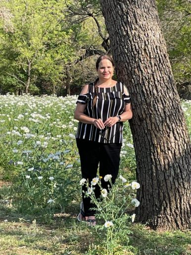 Enjoying Nature: Jenice is casually leaning against a tree in a field of white poppies with a sweet smile on her face. She is wearing black jeans and a black silk top in a cold shoulder style with yellow and white stripes. Her long brown hair is braided and hanging lazily over one shoulder.