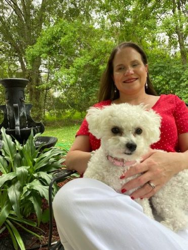 Relaxing in the Garden: Jaz is sitting by a garden of lilies with her bichon puppy, Daisey, in her lap. She is wearing a red shirt with tiny white dots, white pants, and bright red lip color to match.