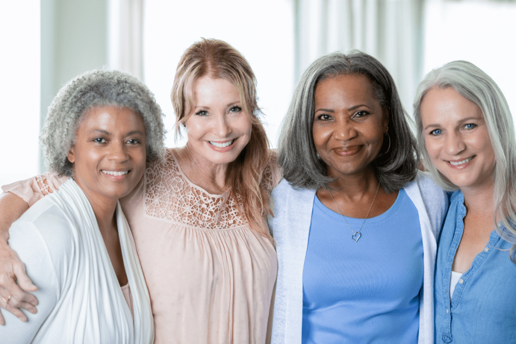 Diverse friendship of four senior women all of whom are facing the camera smiling with arms around one another.