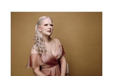 An albino woman with loose curly hair tumbling down her right shoulder looks off to the right smiling slightly. She is wearing a pale pink shimmery off-the shoulder chiffon gown with some slight beading around the sweetheart neckline.She sits against a taupe coloured backdrop.