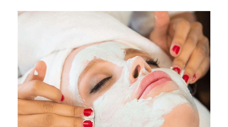 Closeup of an esthetician's hands applying a face mask to a client during a facial.
