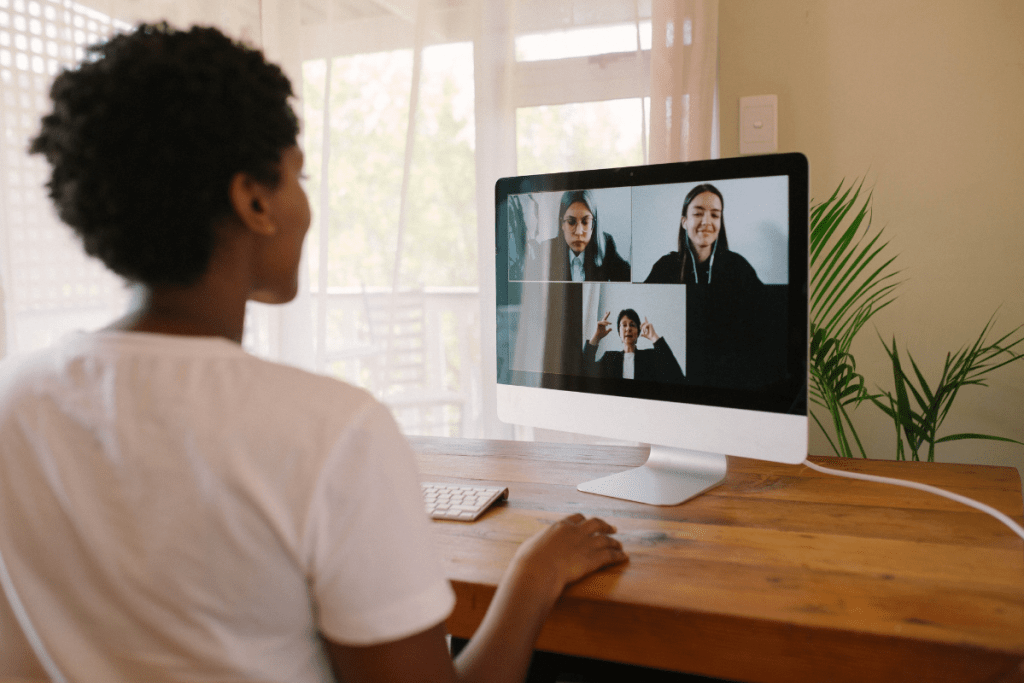 A shot from behind a young African American woman having a virtual meeting on a home computer.