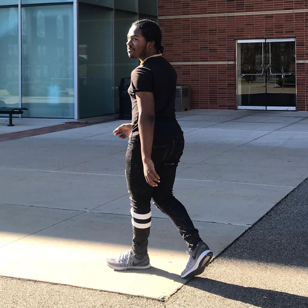 A full-body profile shot of Ryan walking. He's wearing black jeans, a black tee, and gray sneakers.