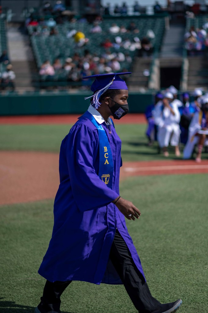 Graduation photo of Ryan wearing a blue cap and gown with a black facemask as he strides to collect his diploma.