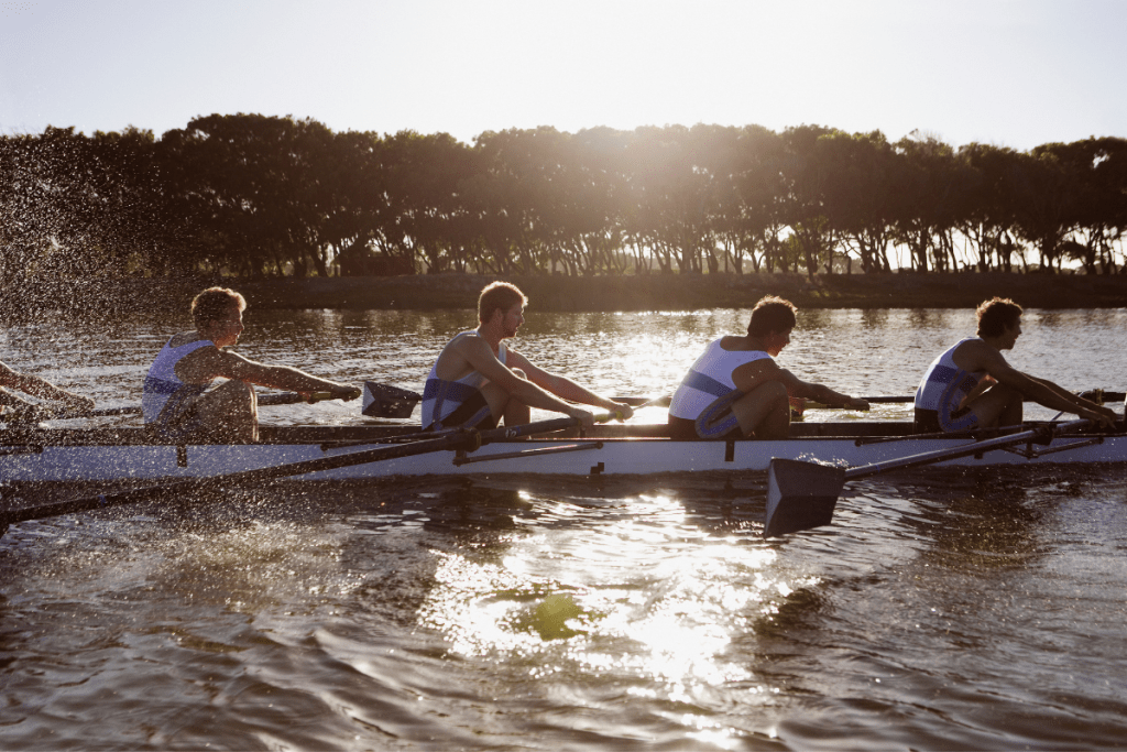 Athletes in a crew rowboat mid stroke.