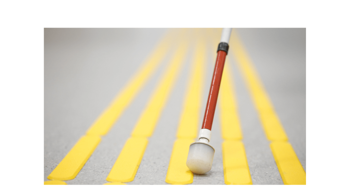 A closeup of a blind pedestrian's white cane while walking and detecting markings on tactile paving with textured ground surface indicators for blind and visually impaired.
