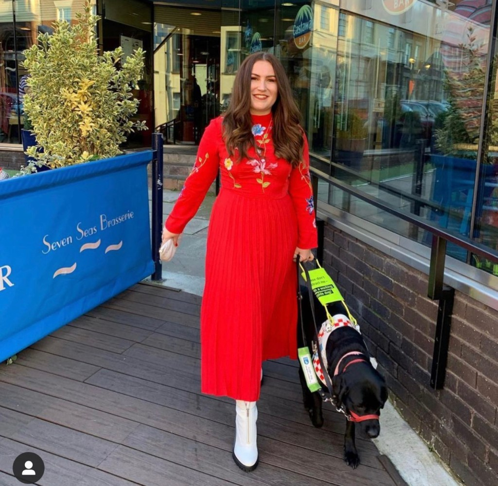 A full length fabulous photo of Molly with brunete hair wearing a red midi dress with white boots being guided by Bella.