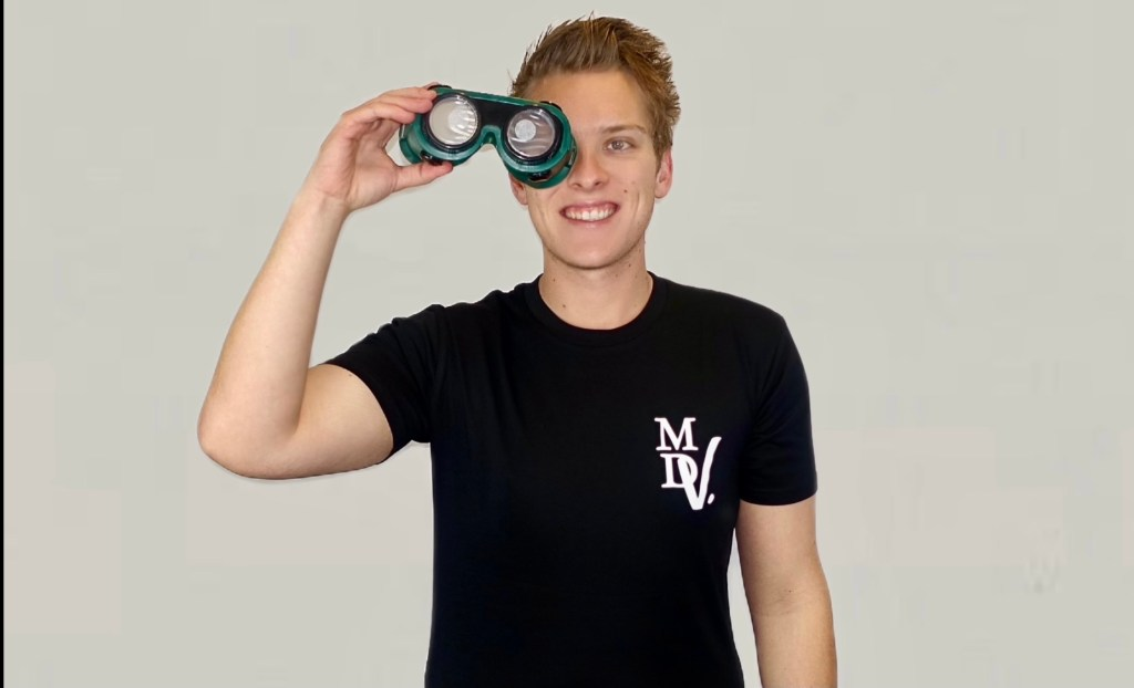 Another shot of Matt in his black MDV tee holding the vision simulation glasses up to his right eye.