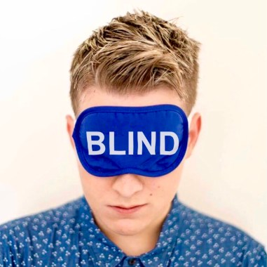 """In this headshot of Matt he is wearing a blue and white shirt with a blue sleepmask with the word """"Blind"""" in white text."""