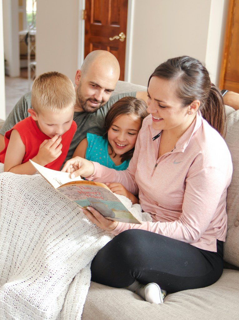Caitlyn Scaggs reading book with family