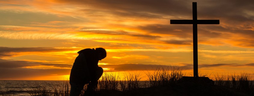 Man praying in front of cross at sunset