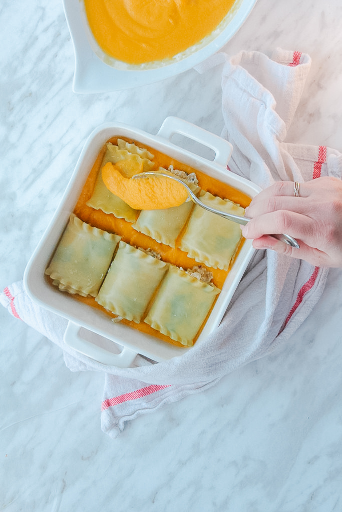 Spreading the butternut squash sauce on the roll ups in a dish.