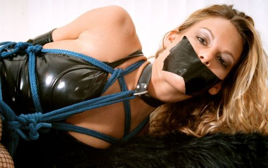 Beautiful Blonde in PVC Gets Collared, Tape Gagged and Tightly Bound