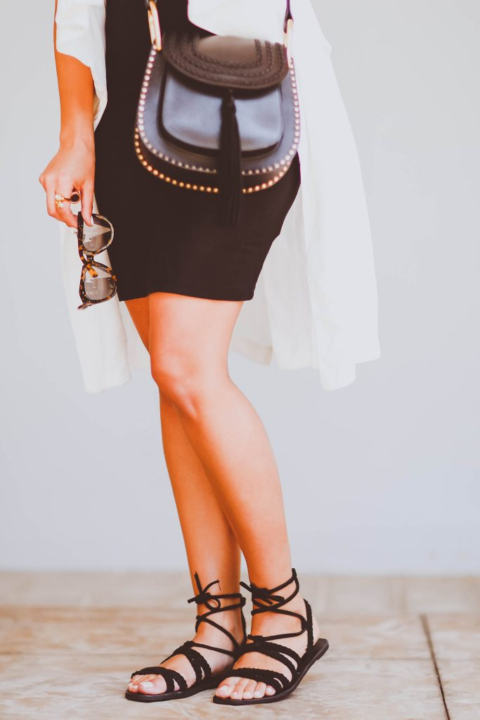casual yet chic mom outfit, summer outfit, white sleeveless vest, black bodycon dress, straw boater hat, black strappy flat sandals, chloe hudson crossbody bag, karen walker number one sunglasses, choker necklaces, cool mom, charlotte tilbury bond girl lipstick