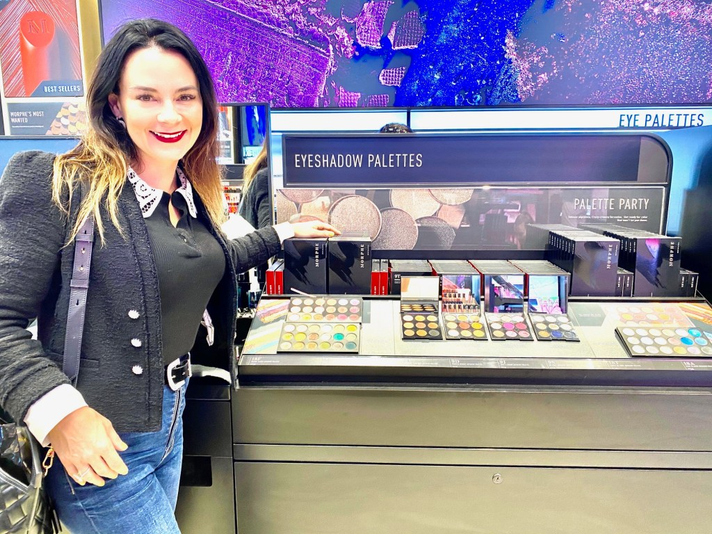 brunette woman lookign at eyeshadows at cosmetic counter Morphe.
