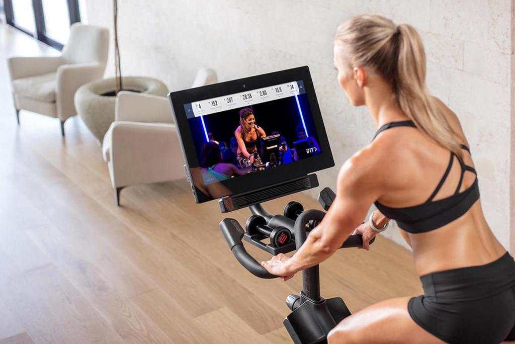 Woman exercising on Peloton bike.
