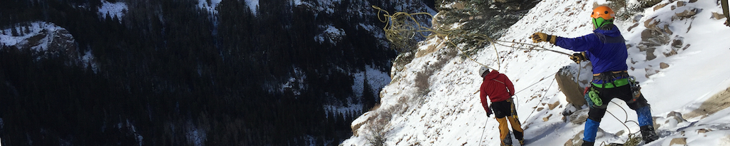 An ice climber throwing a rope over the edge.