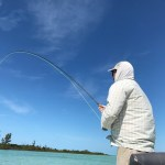 fisherman with bent rod fish on