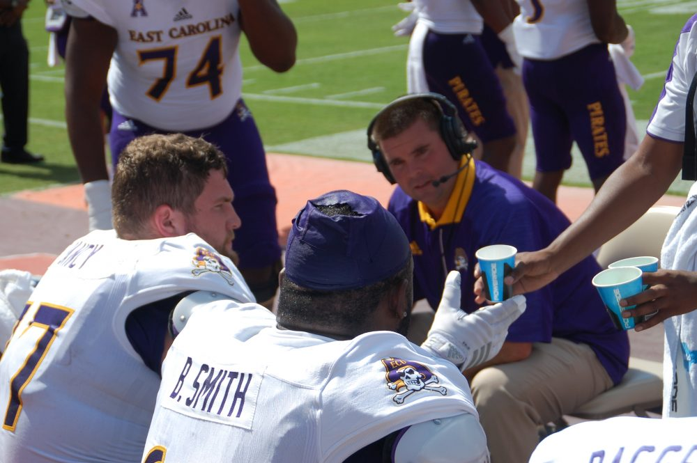ECU offensive line coach Geep Wade makes some adjustments on the sideline. (Photo by Al Myatt)