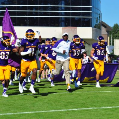 Head Coach Scottie Montgomery and versatile senior James Summers (11) lead the Pirates on the field for an AAC matchup with UCONN (Bonesville Staff photo)