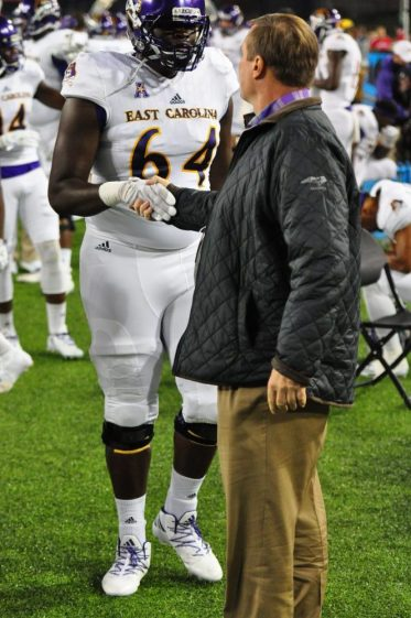 ECU athletic director Jeff Compher greets offensive lineman Des Barmore.