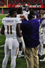 James Summers talks to running backs coach Antonio King.