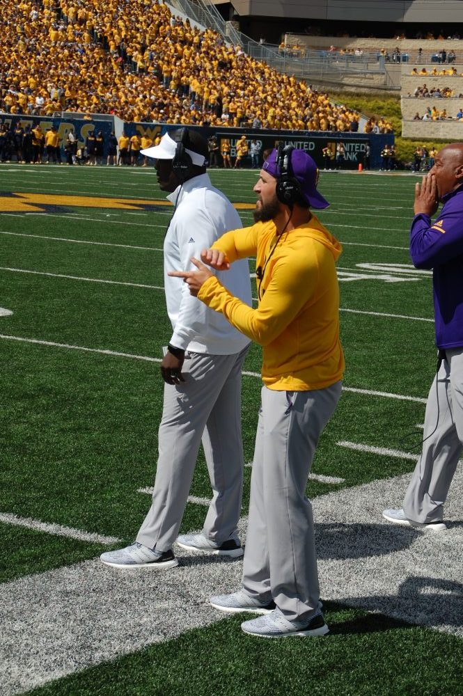 ECU coach Scottie Montgomery (visor) watches from the sideline on Saturday as staffer Damon Magazu makes a signal to the defensive unit. (Photo by Al Myatt)