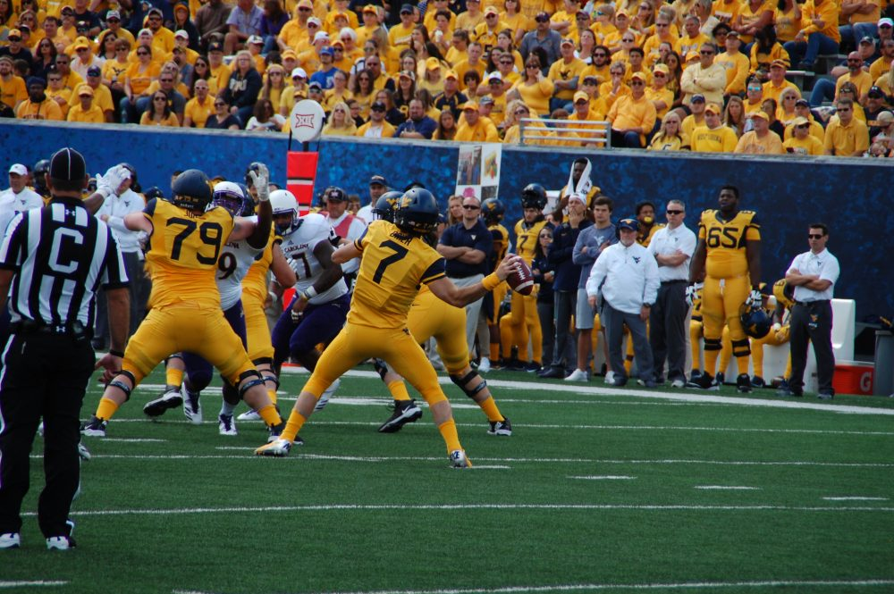 Will Grier of West Virginia uncorks a 52-yard touchdown pass to Marcus Simms. (Photo by Al Myatt)