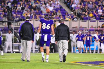 Senior tight end Stephen Baggett is helped off the field but was able to return shortly. (Photo by Al Myatt)