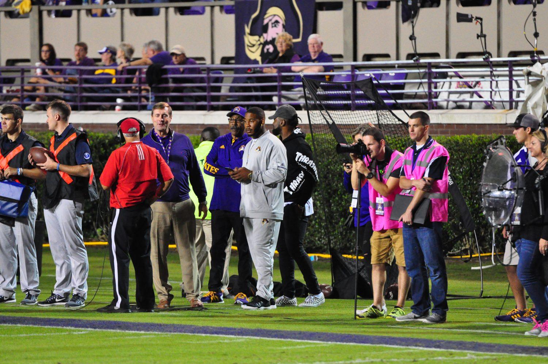 ECU athletic director Jeff Compher and former Pirate linebacker Zeek Bigger are on the ECU sideline. (Photo by Al Myatt)