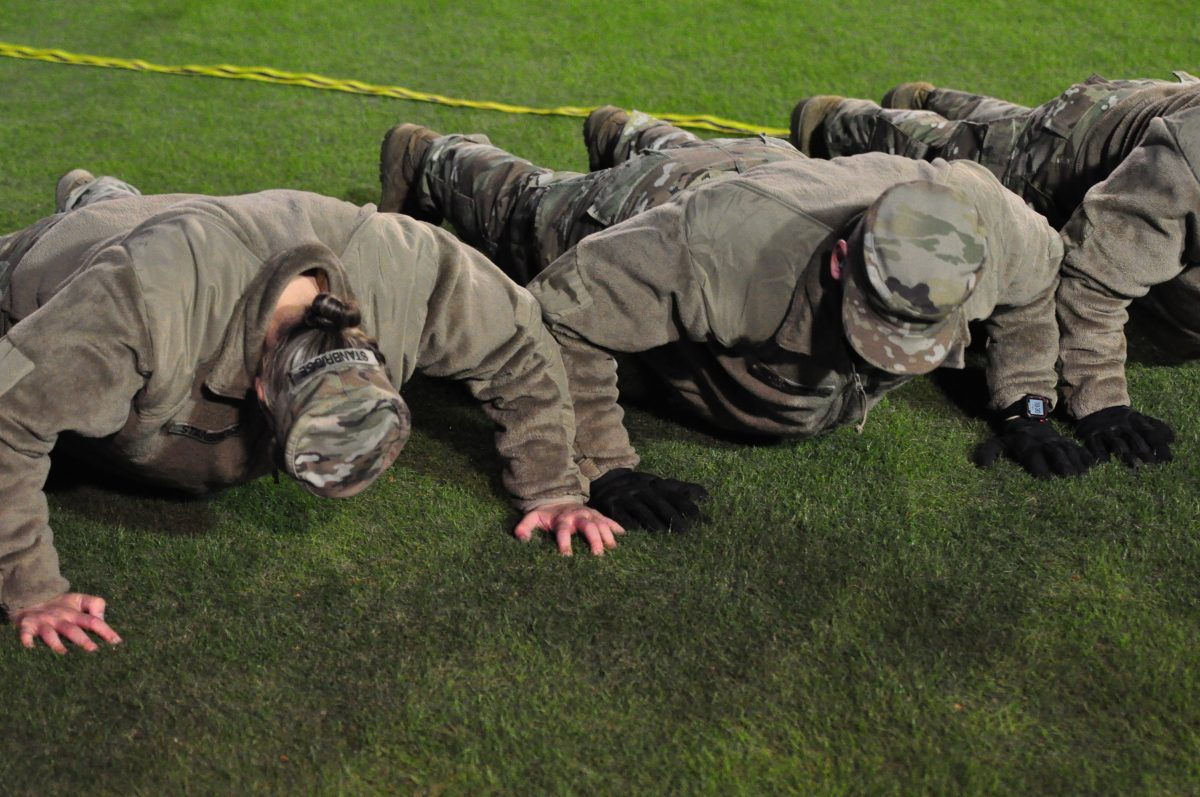 Army ROTC cadets knock out push-ups on Military Appreciation Night after an ECU score. (Photo by Al Myatt)